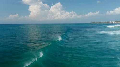 Aerial View of People Surfing Across the Waves in Tropical Blue Ocean