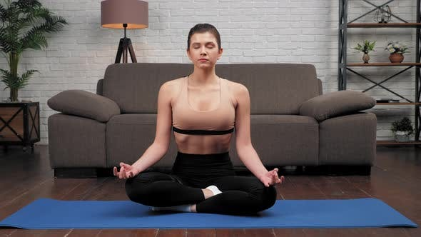 Calm Young Sportive Woman in Sportswear Practices Yoga at Home in Living Room