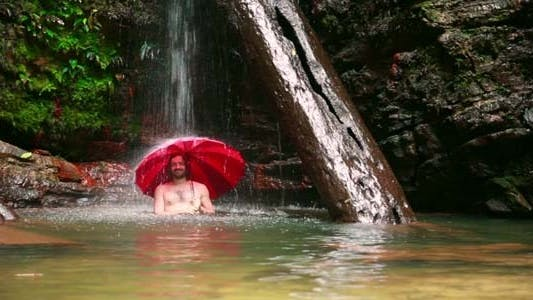 Thumbnail for Man With Umbrella At Waterfall In Borneo