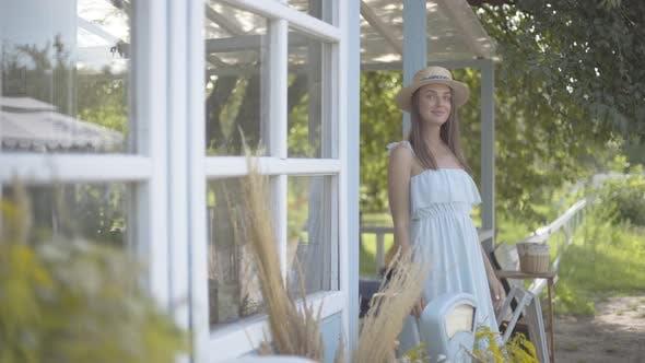 Entzückende junge lächelnde Frau in Strohhut und langes weißes Kleid Blick weg vor der kleinen