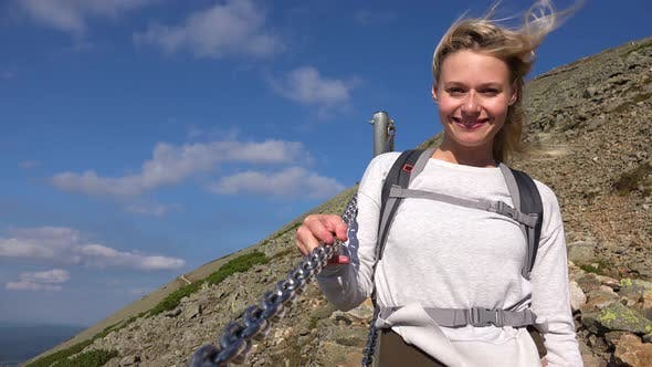 Thumbnail for A Young Beautiful Woman Stands on a Trail on a Hill and Smiles at the Camera