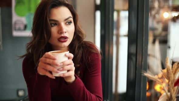 Thumbnail for Brunette Woman Drinking Coffee in Cafe.