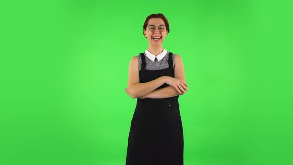 Thumbnail for Funny Girl in Round Glasses Communicates with Someone in a Friendly Manner. Green Screen