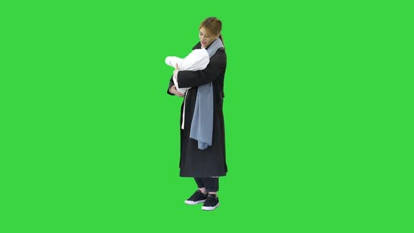 Young Mother with Her Baby Child Outdoors at Winter on a Green Screen, Chroma Key.