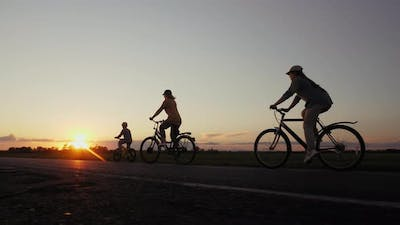 Silhouettes of Mother with Children Ride Bicycles at Sunset