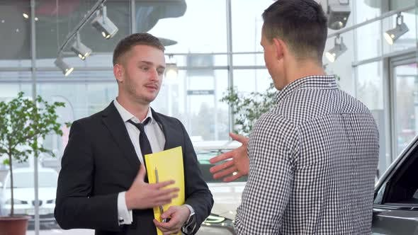 Thumbnail for Car Salesman Giving Car Keys To the Customer After Shaking Hands