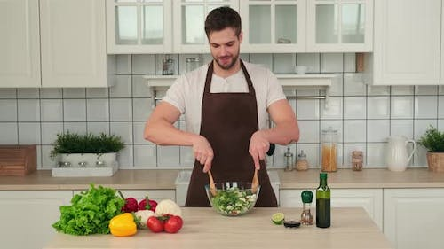 Attractive Man in Apron Stirring Vegan Salad in a Cup While Standing in the Kitchen