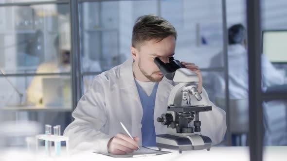Thumbnail for Caucasian Technician Examining Tissue Samples under Microscope