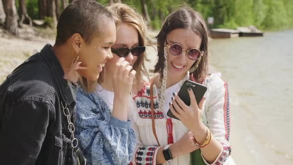 Female Friends Scrolling Photos On Phone