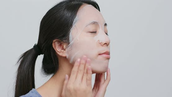 Thumbnail for Young Woman apply face mask on face at home