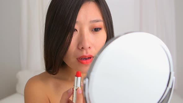 Happy Asian woman applying liptsick