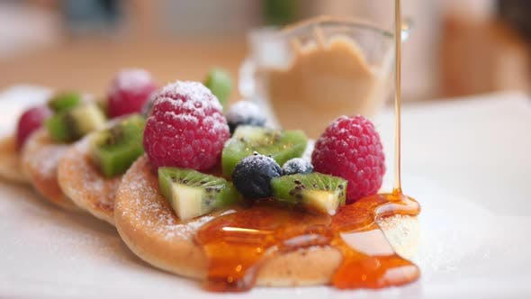 Thumbnail for Pouring Honey Onto Pancakes With Berries And Fruits On Table, Closeup