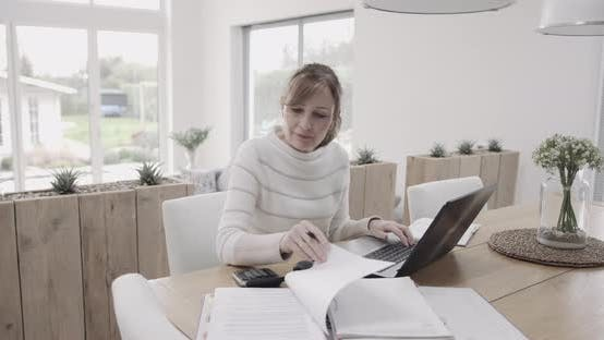 Senior adult woman doing domestic finance on laptop at kitchen table, day in life