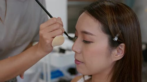 Make up artist do make up on woman face in beauty salon