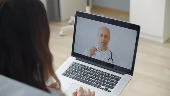 Woman Using Laptop and Talking Online with General Practitioner