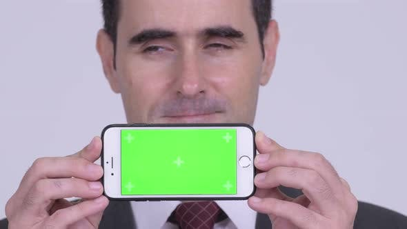 Thumbnail for Closeup of Happy Handsome Businessman Thinking While Showing Phone
