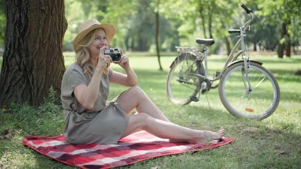 Joyful Caucasian Middle Aged Woman Taking Photos on Camera in Sunny Summer Park