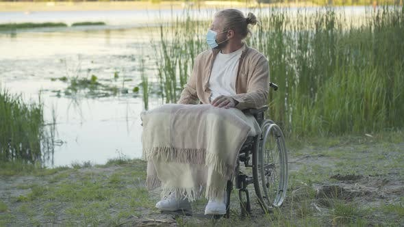 Wide Shot Portrait of Paralyzed Man on Wheelchair in Face Mask Resting on River Bank at Sunset
