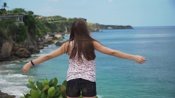 Thumbnail for Girl Standing on a Cliff and Looking at the Sea. Bali, Indonesia