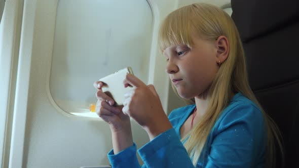 The Child Plays on the Smartphone in the Cockpit