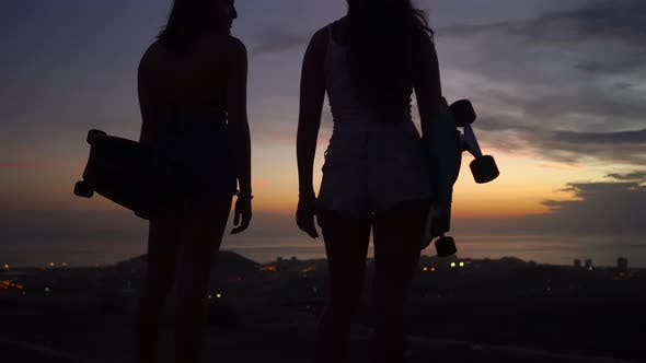 Thumbnail for Two Girls Standing on the Edge of the Road with Skateboards in Their Hands Watching the Sunset