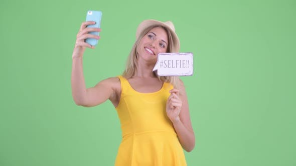 Thumbnail for Happy Young Blonde Tourist Woman Taking Selfie with Paper Sign