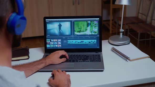 Videographer Working with Video Footage on Laptop