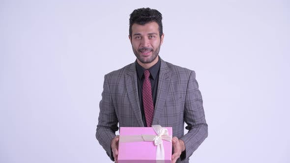 Thumbnail for Happy Bearded Persian Businessman Giving Gift Box