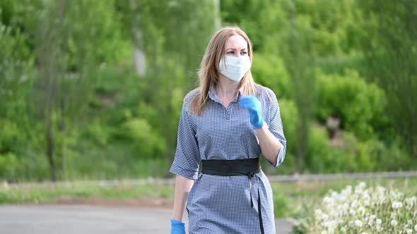 Thumbnail for a Girl Wearing Gloves in the Street Takes Off Her Medical Mask. Protection Against the Covid-19