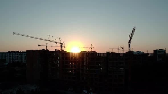 Thumbnail for Aerial Drone View of Silhouette Construction Cranes in Sunset Light. Construction Site Building in