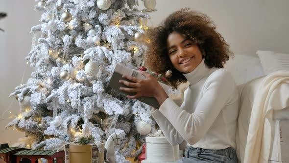Lady Holds Present Box Against Designer White Christmas Tree