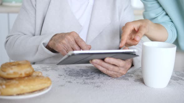 Hands Of Grandmother And Granddaughter Using Tablet Computer
