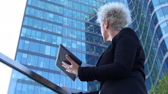 Thumbnail for A Middle-aged Businesswoman Works on a Tablet in an Urban Area - a Windowed Office Building