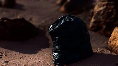 Black Plastic Garbage Bags Full of Trash on the Beach