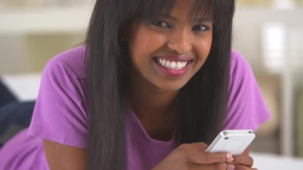 Thumbnail for African American girl smiling with mobile phone in hands