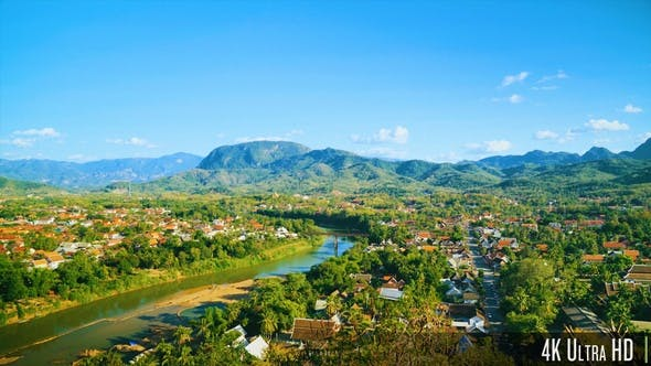 Cover Image for 4K Overhead View of a Small City or Town Near a River with Views of Mountainous Landscape