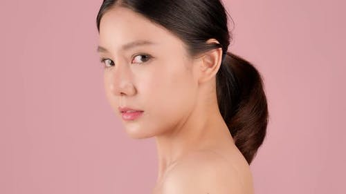 Close up Beauty shot of Beautiful Asian girl looking at camera isolated on pink background