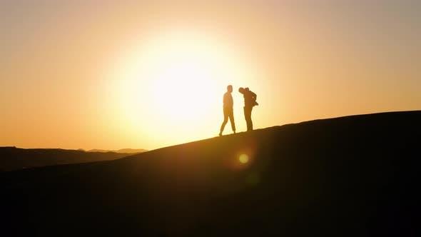Thumbnail for Silhouettes of Two Men in The Desert Against Sunset