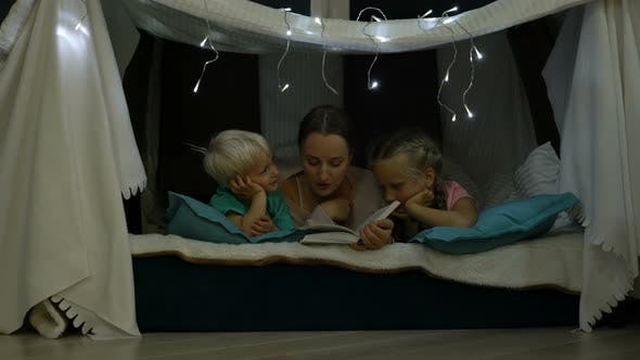 Mother Reads a Bedtime Story for Children