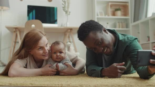 Thumbnail for Happy Multiethnic Spouses Making Selfie with Child