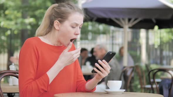 Thumbnail for Young Woman Upset by Loss on Smartphone, Sitting in Cafe Terrace