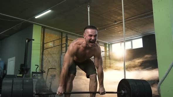 Junge starke Mann schreien und tun Kreuzheben Übung im Fitnessstudio
