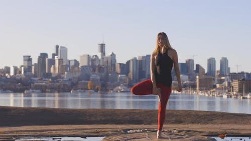 Woman Does A Yoga Tree Pose With Lake City Skyline Background