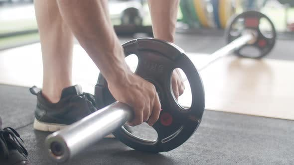 Young athlete caucasian guy exercising doing deadlift a barbell over his head fat burning workout.