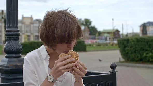 Cover Image for Businesswoman Eating Burger and Using Tablet Outdoors