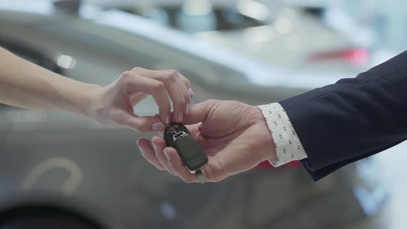 Thumbnail for Male Hand Gives a Car Keys To Famale Hand in the Car Dealership Close Up. Unrecognized Auto Seller