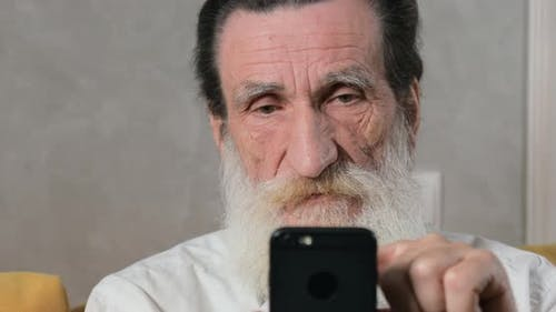 Senior Man Gets Confused with Smartphone