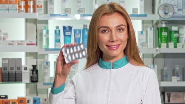 Thumbnail for Weibliche Apothekerin lächelnd hält Blister von Kapseln bei Drogerie