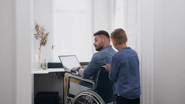 Thumbnail for Small Boy Running to His Confident Positive Smiling Bearded Young Dad in Wheelchair which Working