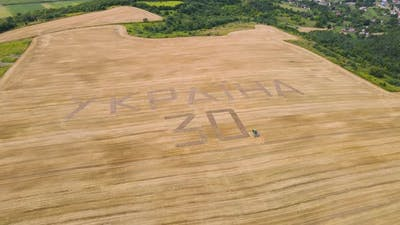 A Tractor Plowed An Inscription Dedicated To The Independence Day Of Ukraine On A Wheat Field